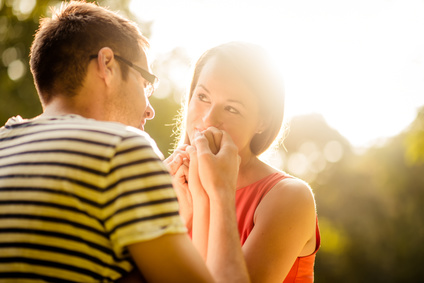 Intimate moments - young couple hugging in nature against sun